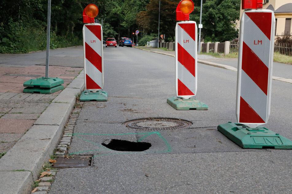 Unwetterschäden: Die Bürgerstraße in Chemnitz wurde durch heftige Regenfälle unterspült. Ein kleines Loch ist auf der Fahrbahn zu sehen.