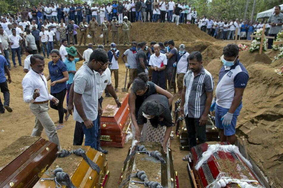 Anusha Kumari (M,unten) nimmt während einer Massenbestattung Abschied von ihrem Mann, zwei Kindern und drei Geschwistern .
