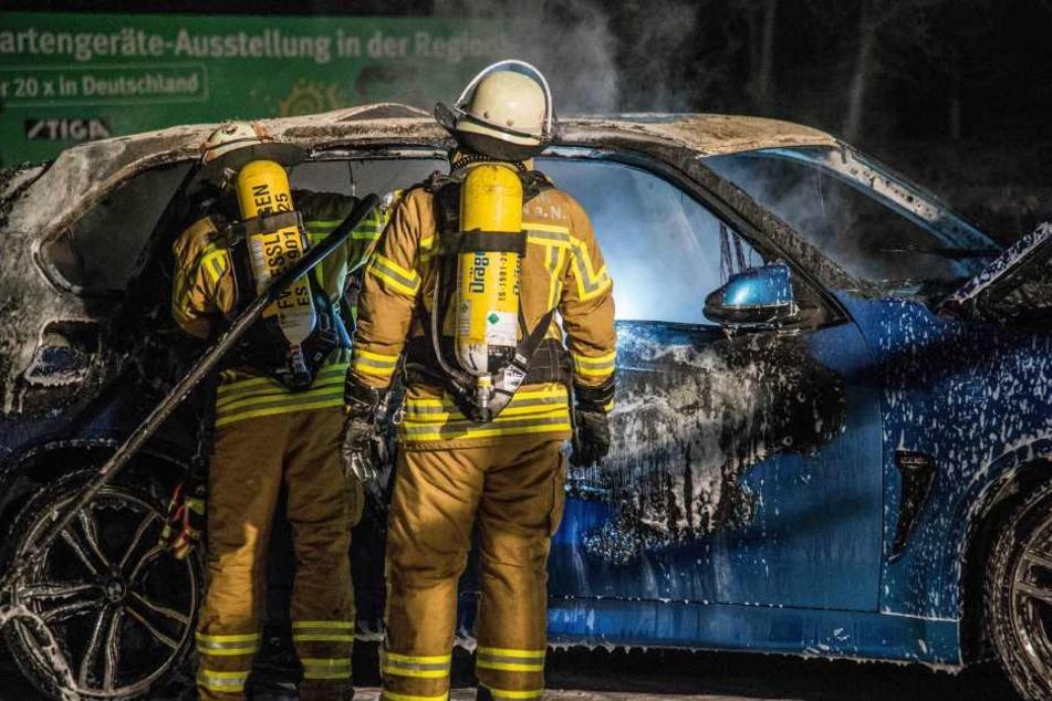 Mittels Schaum schafft es die Feuerwehr, das Feuer im SUV zu löschen.