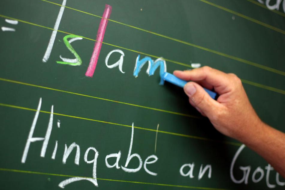 Ein Religionslehrer schreibt an einer Schule während des islamischen Religionsunterrichts an der Tafel. (Archivbild)