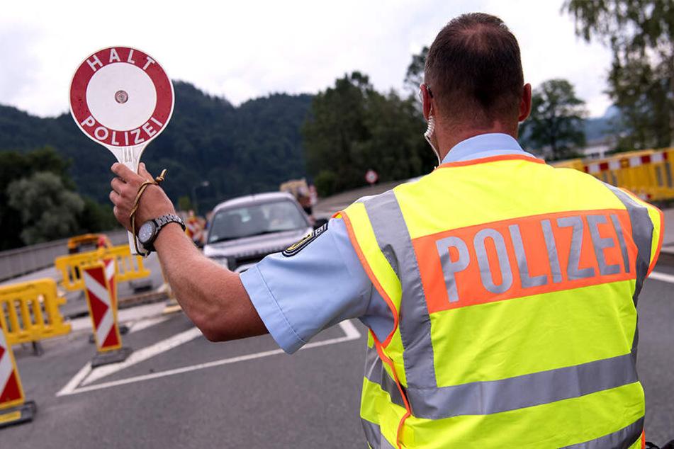 Ein Grenzpolizist stoppt ein herannahendes Auto zur Kontrolle.