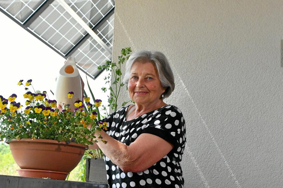 Bewohnerin Sonja Wendler (80) auf ihrem Balkon mit Solarpaneelen.