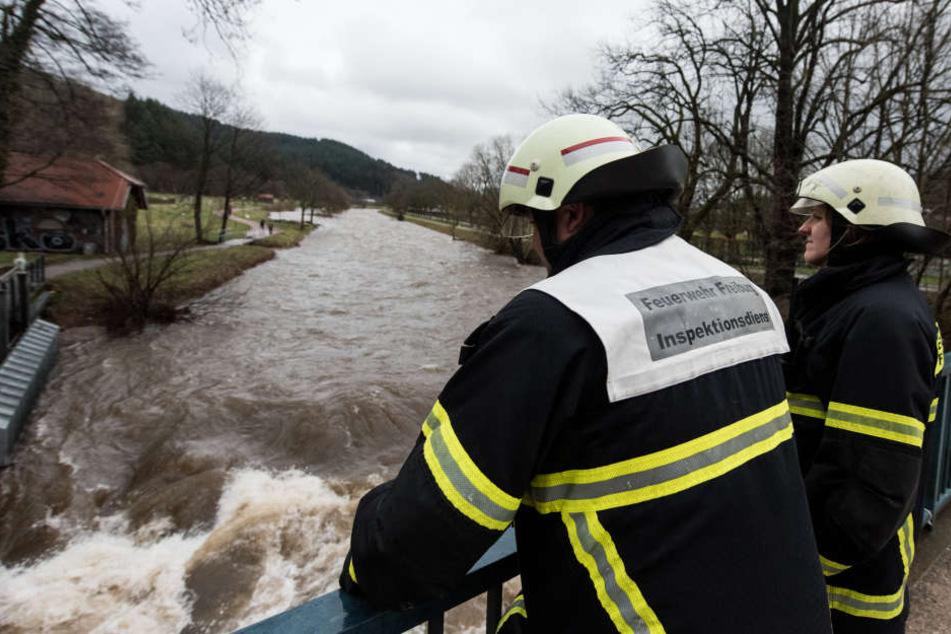 Feuerwehrleute kontrolliert in Freiburg die Dreisam bei Hochwasser.