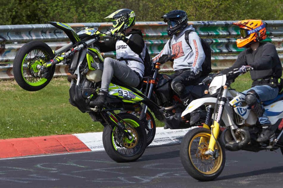 """Ein Motorradfahrer fährt beim Korso zum Saisonauftakt unter dem Motto """"Anlassen"""" auf dem Nürburgring auf dem Hinterrad."""