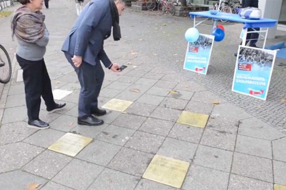 Die Wehrmachtsstolpersteine sind im Boden eingelassen, im Hintergrund steht der falsche AfD-Stand.