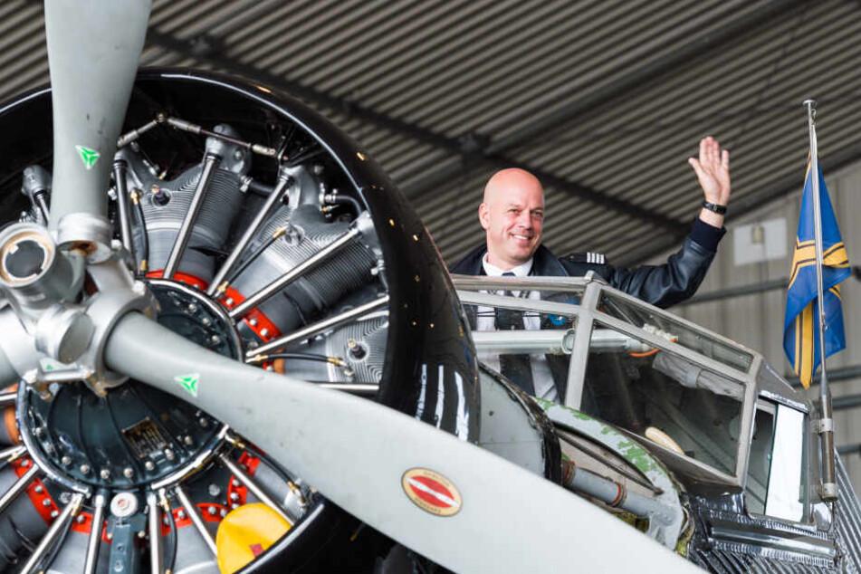Uwe Wendt, Chefpilot der Ju 52 winkt in Hamburg im Hangar auf der Lufthansa Basis Hamburg aus dem Cockpit des Flugzeugs.