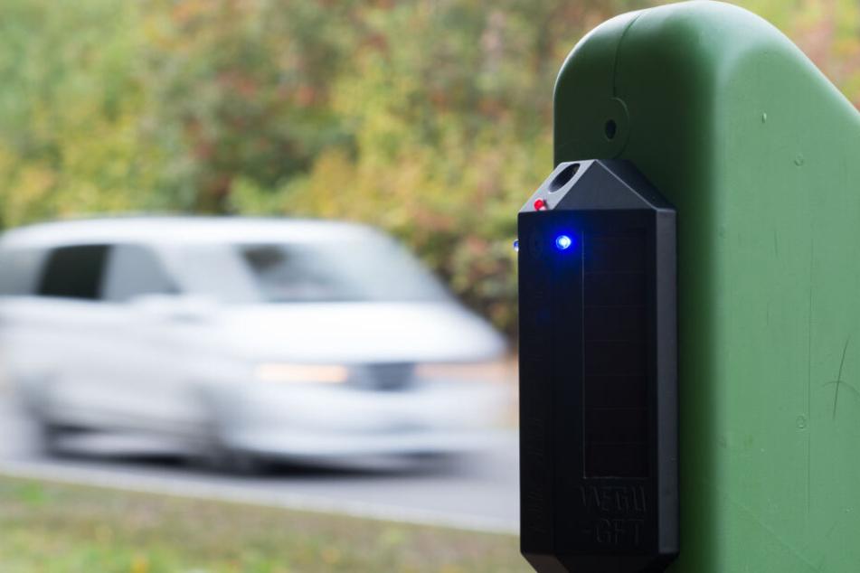 Ein an einem grünen Trägerpfosten montierter Wildwarner gibt als sich ein Fahrzeug nähert ein akustisches und optisches Signal ab. Die Signale wirken verstörend auf Wild und sollen die Tiere am Queren der Straße hindern.