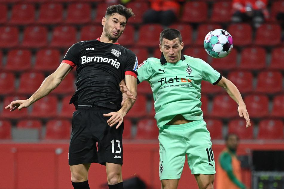 Leverkusens Stürmer Lucas Alario (28, l.) und Mönchengladbachs österreichischer Verteidiger Stefan Lainer (28) kämpfen um den Ball.
