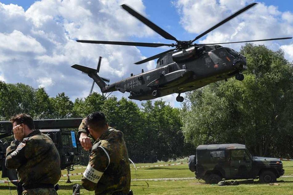 Ein Hubschrauber Sikorsky CH-53GS der Luftwaffe macht mächtigen Wind bei der Landung auf einer Wiese in Storkow.