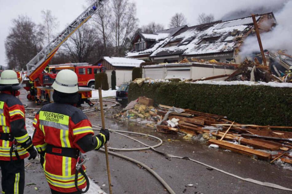 Zwei Feuerwehrleute stehen am Sonntag vor dem zerstörten Haus.