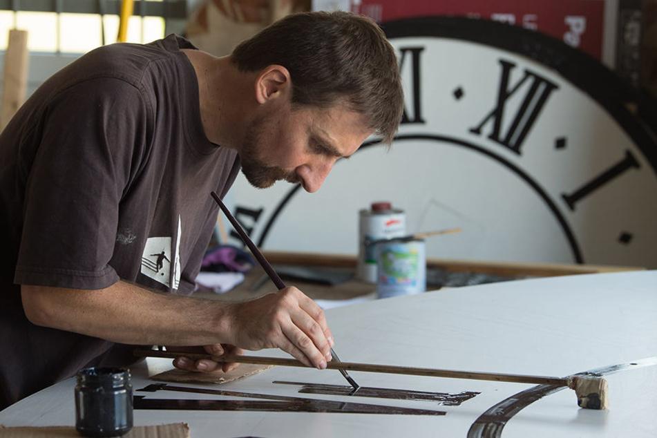 Uhrentechniker Tobias Vogler zeichnet die römischen Ziffern auf das Ziffernblatt.