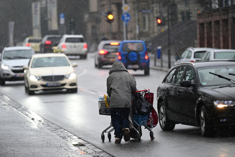 Autos weichen einer obdachlosen Frau aus, die ihr Hab und Gut in einem Einkaufswagen am Rande einer Fahrbahn einer Straße schiebt.