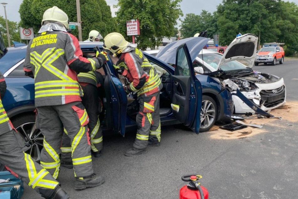 Die Kameraden der Feuerwehr stehen an der Unfallstelle. Beide Autos sind stark beschädigt.