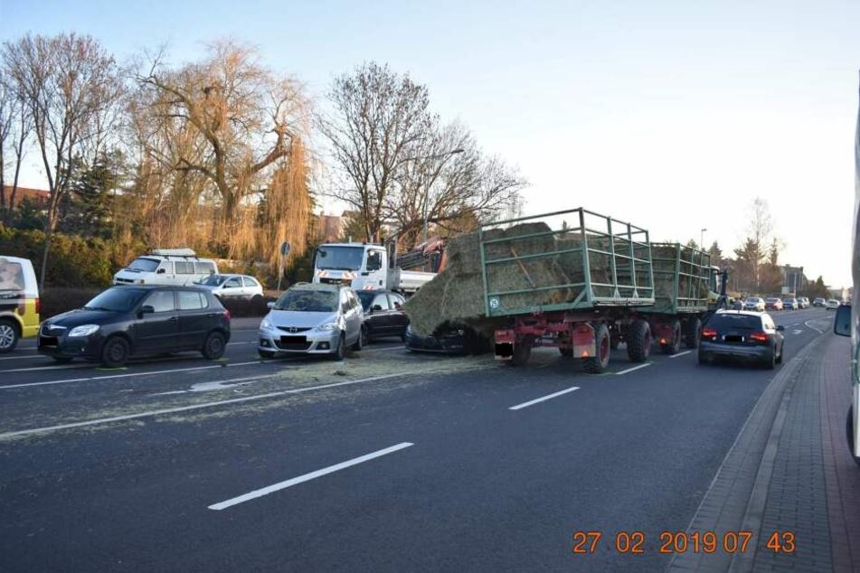 Hups! Aufgrund mangelnder Ladungssicherung sind zwei Heuballen von diesem Traktor gerutscht und haben vier Autos zusammengeschoben.