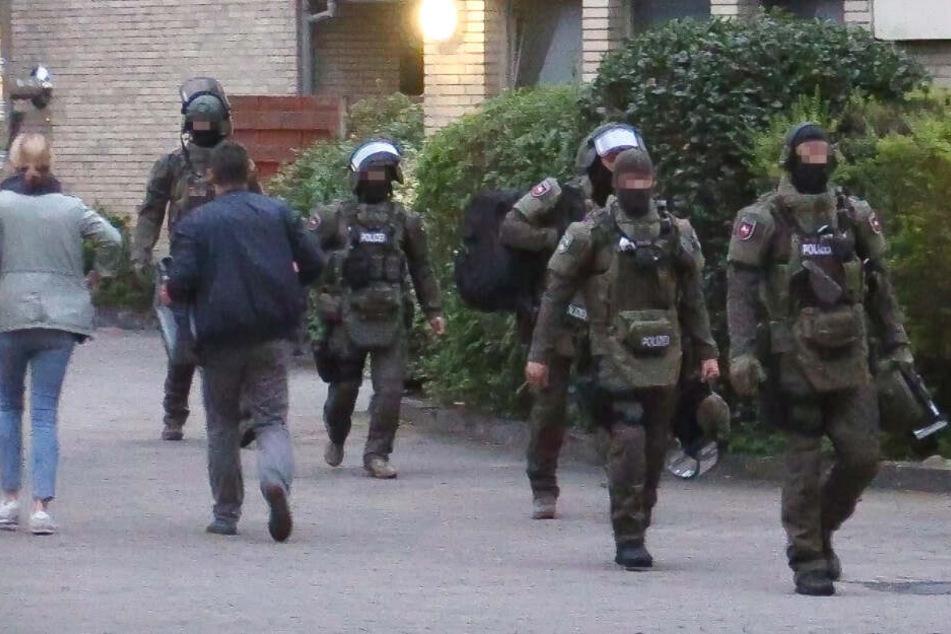 Mitglieder des SEK kommen aus der gestürmten Wohnung zurück.