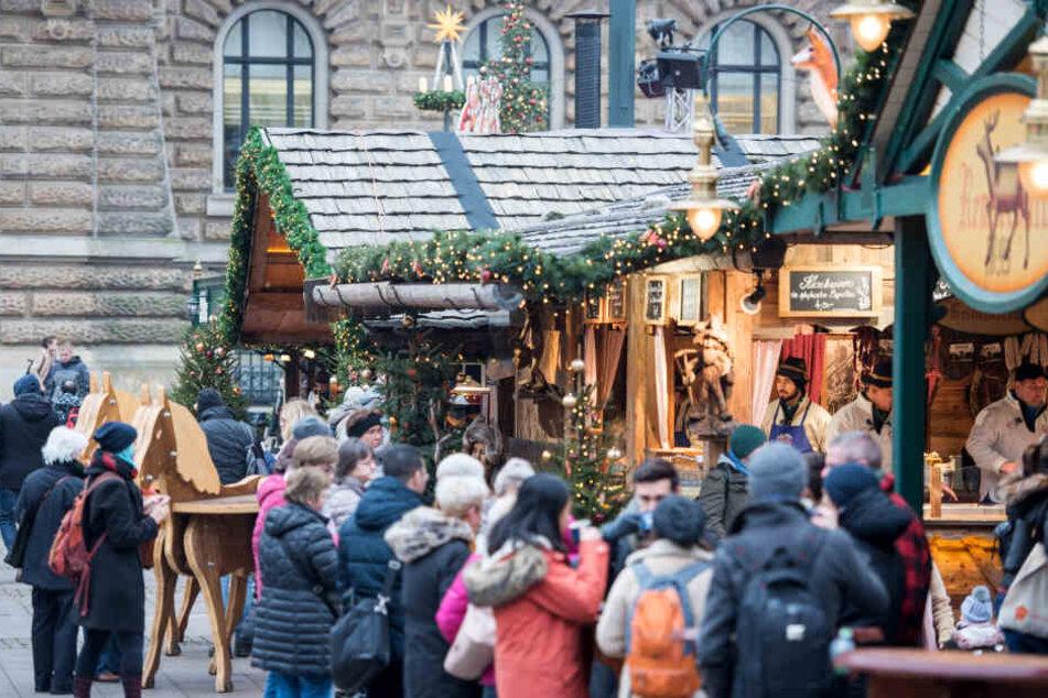 Besucher gehen über den Weihnachtsmarkt auf dem Rathausmarkt.