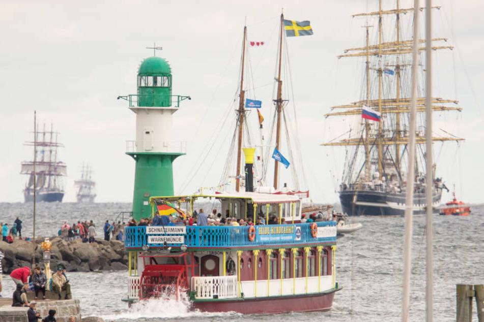 Großsegler, Traditionsschiffe und Ausflugsdampfer fahren vor der Warnemünder Mole zur traditionellen Ausfahrt der Hanse Sail.