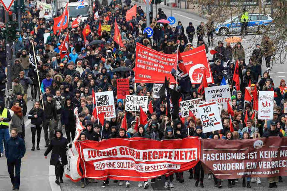"""Teilnehmer einer Demonstration des """"Bündnisses gegen Rechts"""" gehen mit Bannern und Plakaten zum Bahnhof Dammtor."""