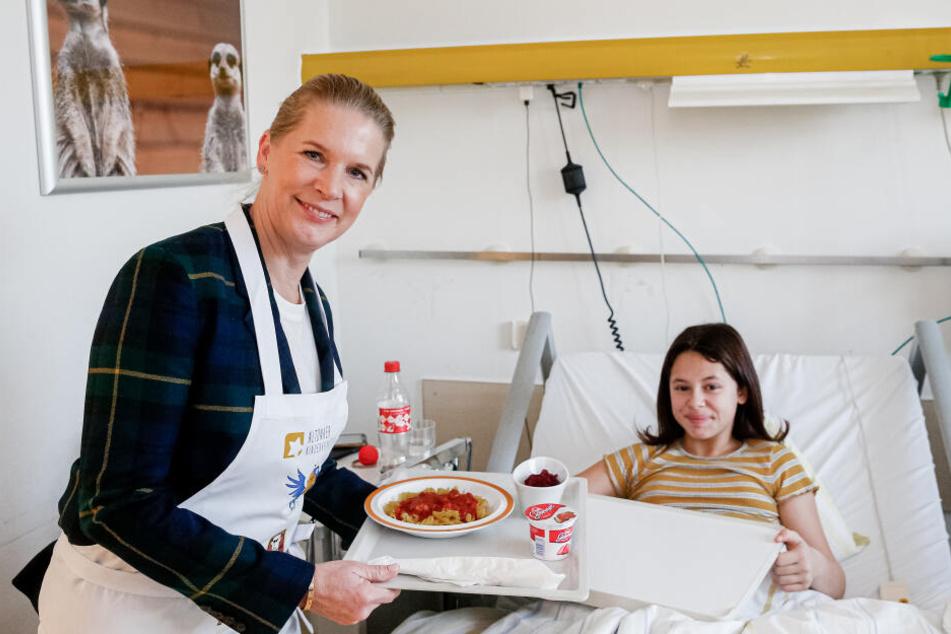 Cornelia Poletto serviert der 11-jährigen Emily das Mittagsessen.