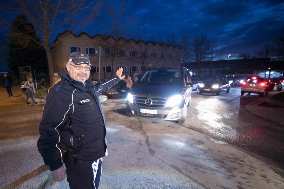 """Polizeischutz für die Schulen """"Am Marienschacht"""" in Bannewitz: Polizeiobermeister Bernd Neumann (51) reguliert den Verkehr, weist Autofahrer durch das Nadelöhr."""