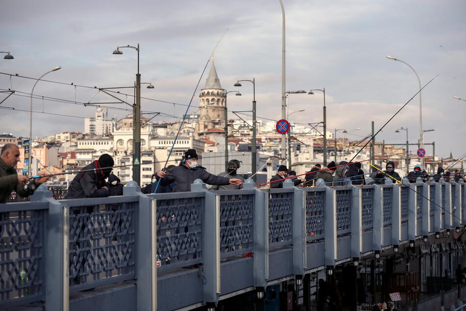 Angler - mal mit und mal ohne Corona-Maske - auf der Galata-Brücke in Istanbul: Die Infektionszahlen in der Türkei steigen immer weiter an.
