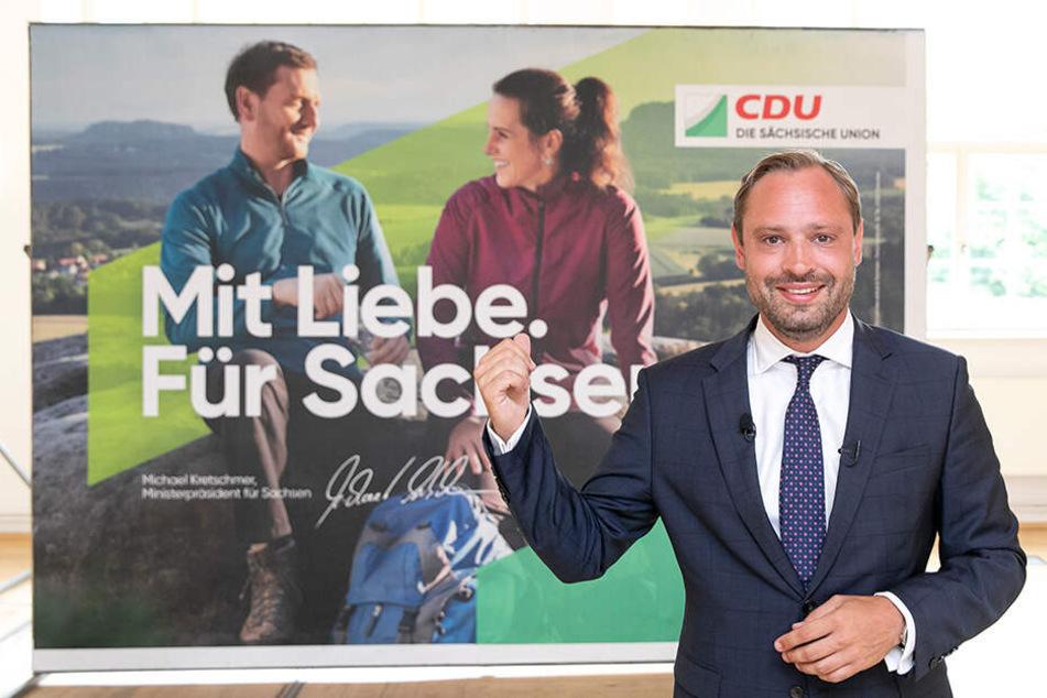 """""""Mit Liebe für Sachsen"""": CDU-Generalsekretär Alexander Dierks (31) präsentiert das Plakat mit Michael Kretschmer (44) und seiner Lebensgefährtin."""