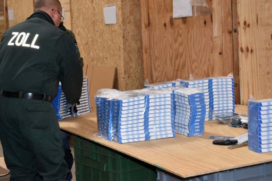 Ein Beamter sortiert gefundene Handyhüllen.