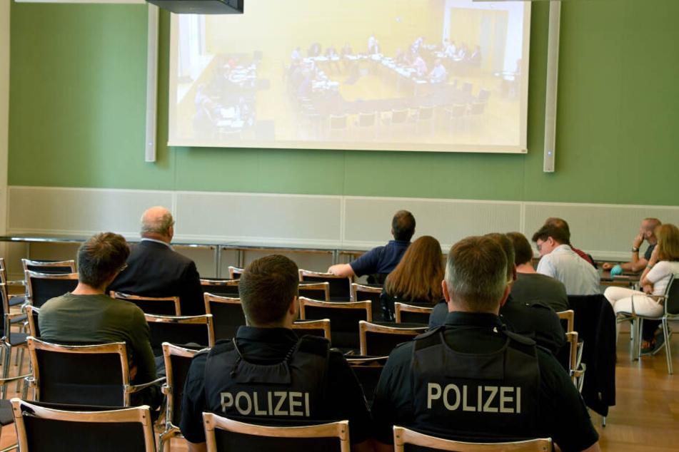 olizisten und Zuhörer verfolgen im Landtag die Videoübertragung der Sitzung des Parlamentarischen Untersuchungsausschusses zur Rocker-Affäre.
