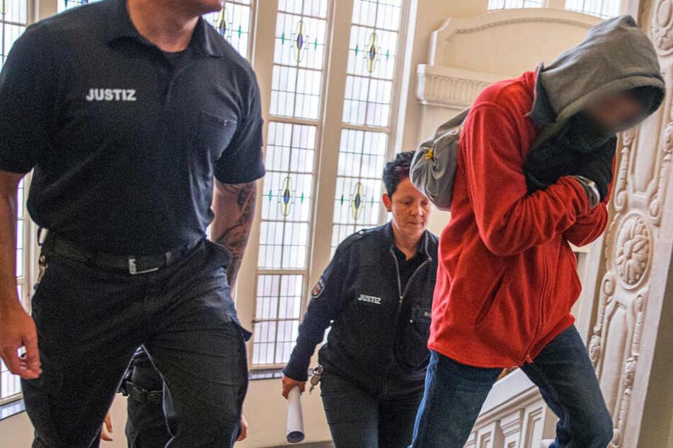 Justizbeamte führen den Angeklagten in den Gerichtssaal.