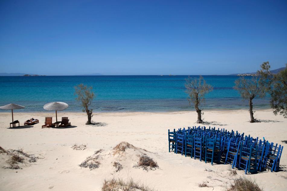 Ein Tourist genießt die Sonne, während Tavernenstühle am Strand von Plaka auf der Ägäisinsel Naxos gelagert werden. Am 15. Mai wird in Griechenland offiziell die Tourismus-Saison eingeläutet.