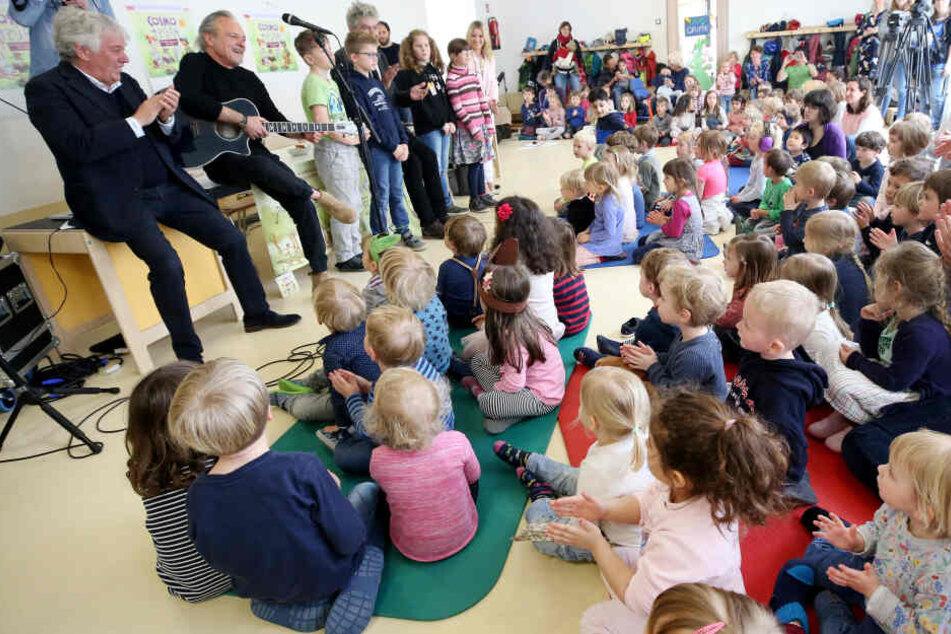 Kinderliedermacher Rolf Zuckowski und das Autorenteam Dieter Faber und Wolfram Eicke (oben v.l) stellen den Kindern einer Kita ein neues Hörspiel vor.
