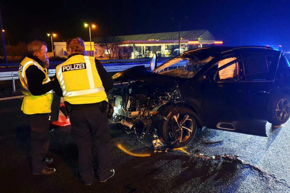 Polizisten stehen vor dem verunfallten Fahrzeug.