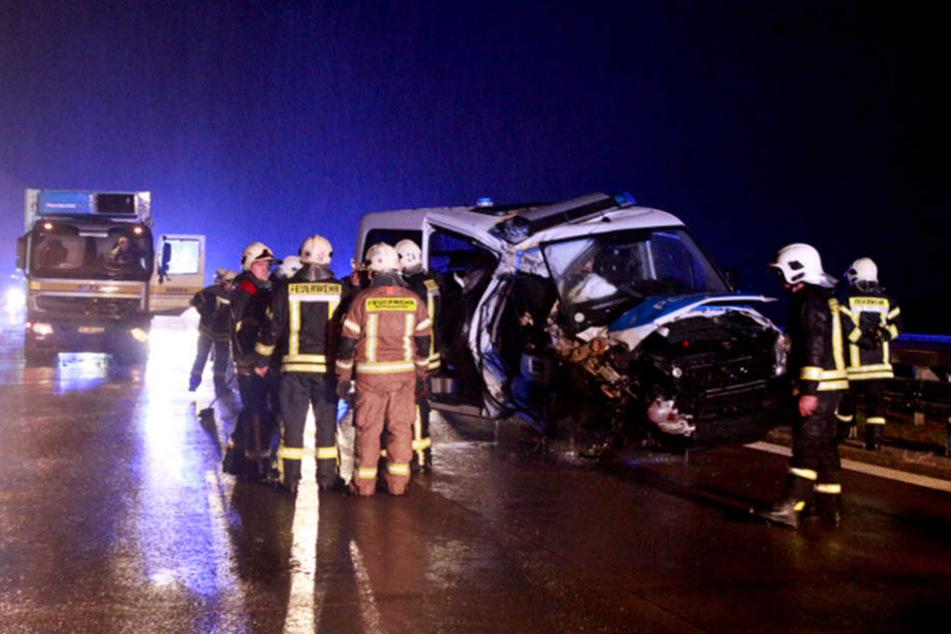 Feuerwehrleute stehen neben einem verunfallten Fahrzeug der Polizei auf der Autobahn 12 (A12).