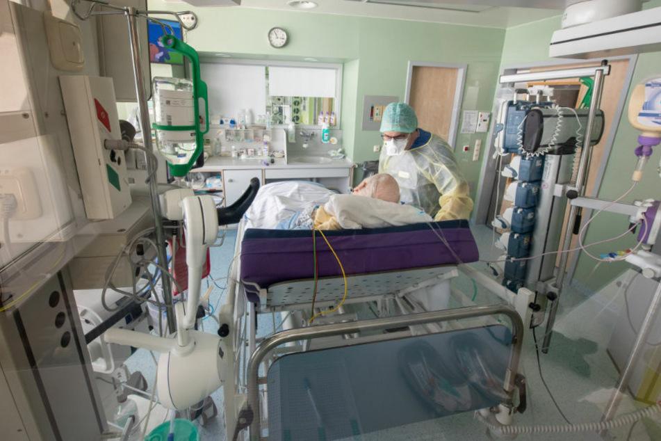 Ein Arzt untersucht in Schutzkleidung in einem isoliertem Intensivbett-Zimmer einen positiv getesteten Corona-Patienten. In Brandenburg sind zwei weitere Menschen an dem Virus gestorben (Symbolfoto)