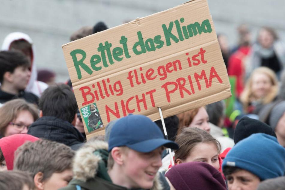 """Teilnehmer an der """"Fridays for Future"""" - Klimastreikdemo in Berlin halten Plakate hoch."""