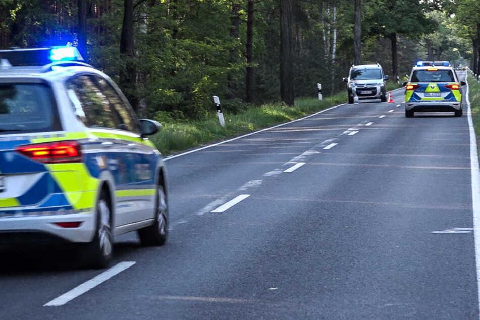 Polizeifahrzeuge stehen auf der Bundesstraße 179 an dem Ort, wo die 81-Jährige in die Gruppe von Fahrradfahrer fuhr.