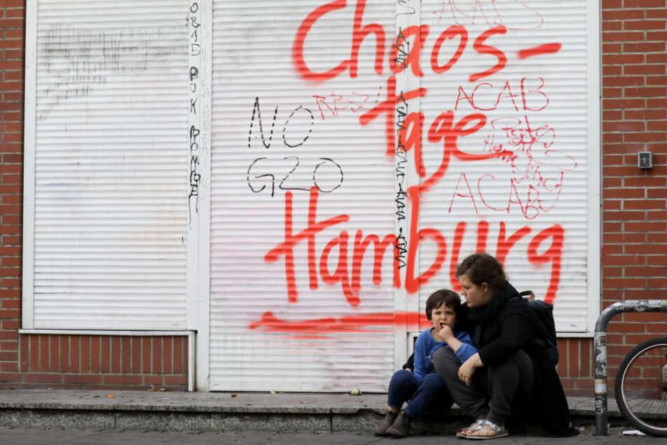 Nach den Ausschreitungen: Eine Mutter und ihr Kind sitzen am 8. Juli vor einem Ladenlokal.