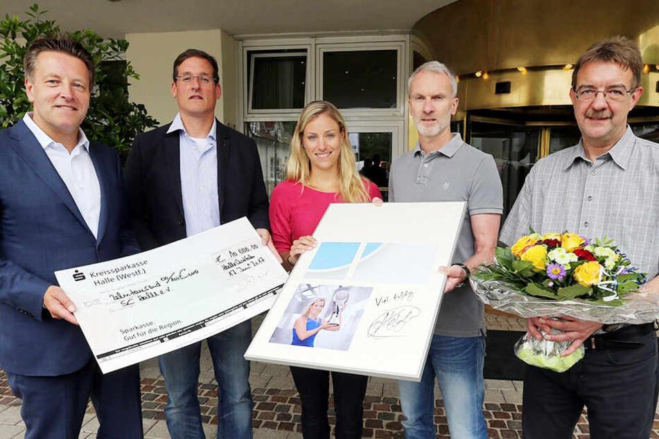 Turnierdirektor Ralf Weber (links) übergab gemeinsam mit der Weltranglisten-Ersten Angelique Kerber einen 10.000 Euro-Scheck an den SC Halle.