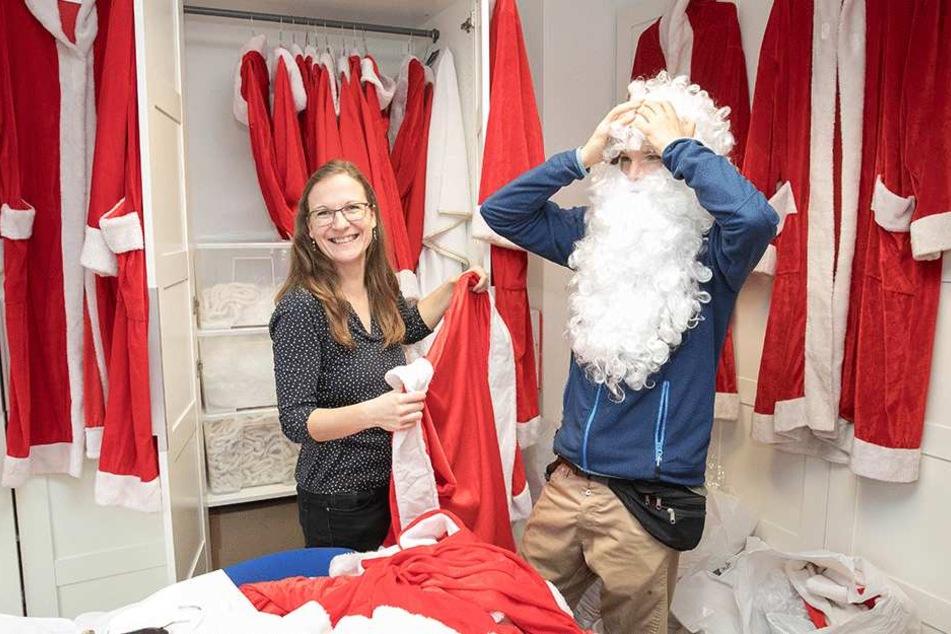 """Die STAV besitzt einen großen Fundus an Kostümen für Engel und Weihnachtsmänner. Peggy Zöllner ist einem """"Santa Claus"""" bei der Anprobe behilflich."""