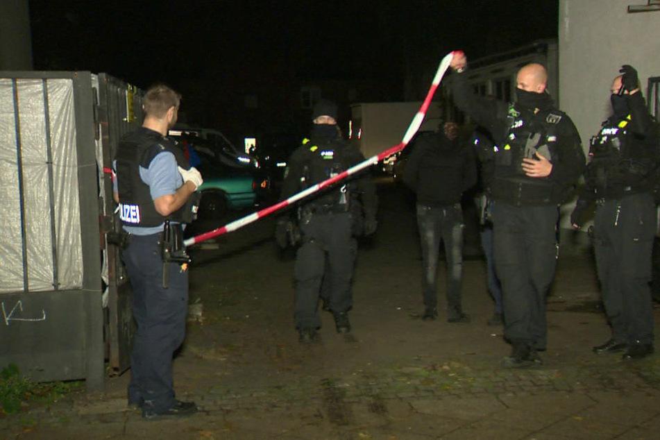 Einer der neun mutmaßlichen Bankräuber wird am Mittwochabend von der Polizei abgeführt.