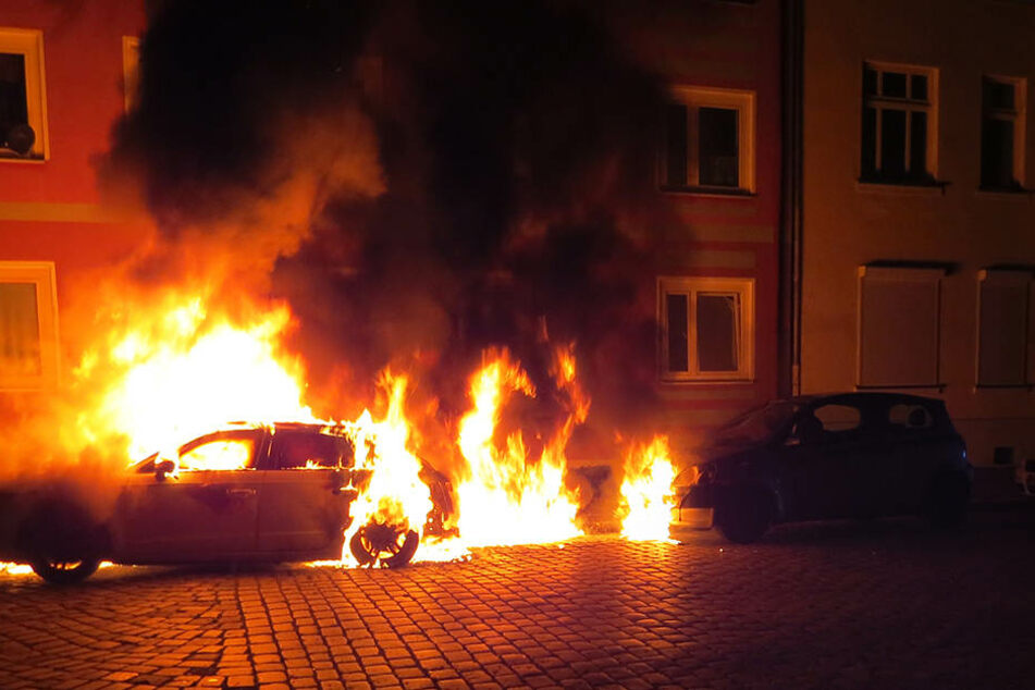 Das Feuer des angezündeten PKW griff auf benachbarte Fahrzeuge sowie die Hausfassade über.
