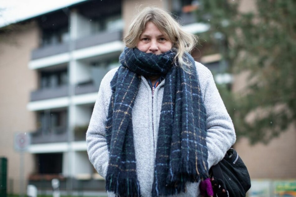 Die Mieterin Daniela Gallien steht mit Schal vor ihrem Wohnhaus.