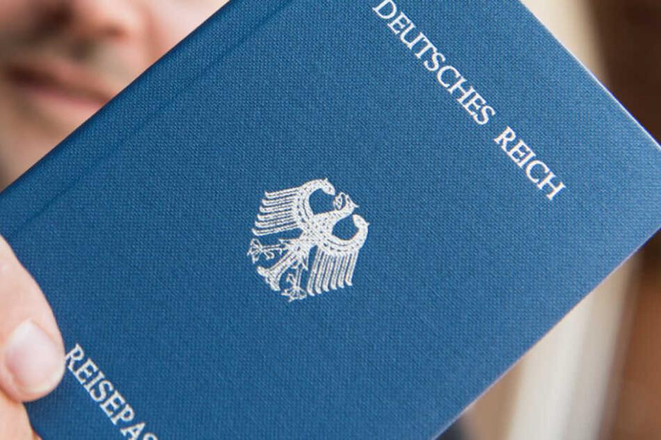 """Ein Mann hält ein Heft mit dem Aufdruck """"Deutsches Reich Reisepass"""" in der Hand. (Archivbild/Symbolbild)"""