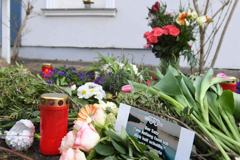Kerzen und Blumen stehen vor dem Eingang des Hauses, in dem am 19.03.2019 eine 18-jährige Frau tot aufgefunden wurde.