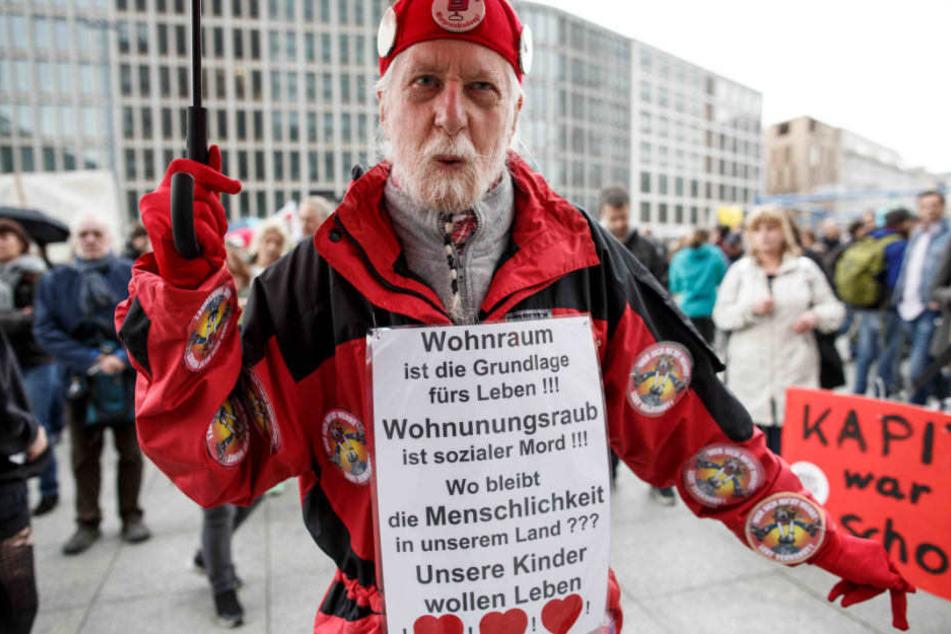 """Einer der Teilnehmer trägt ein Schild, auf dem u.a. steht """"Wohnraum ist die Grundlage fürs Leben!!! Wohnungsraub ist sozialer Mord!!!""""."""