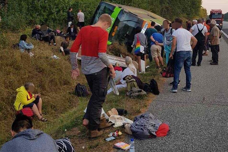 """Reisende sitzen um den verunglückten """"FlixBus"""" auf dem Boden."""