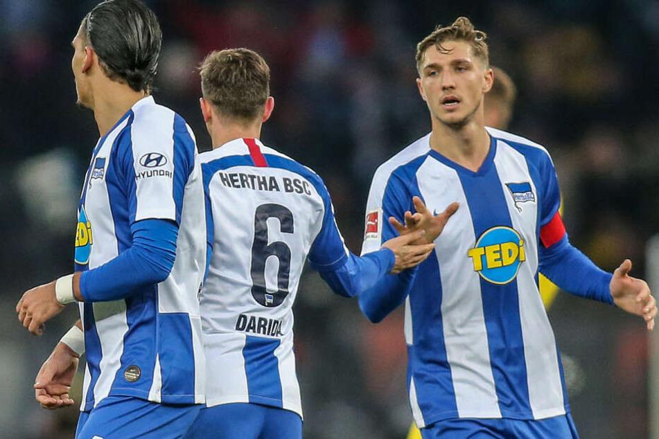 Berlins Niklas Stark (r) und Karim Rekik (l) beglückwünschen Teamkollegen Vladimir Darida (M) nach dessen Treffer gegen Borussia Dortmund.