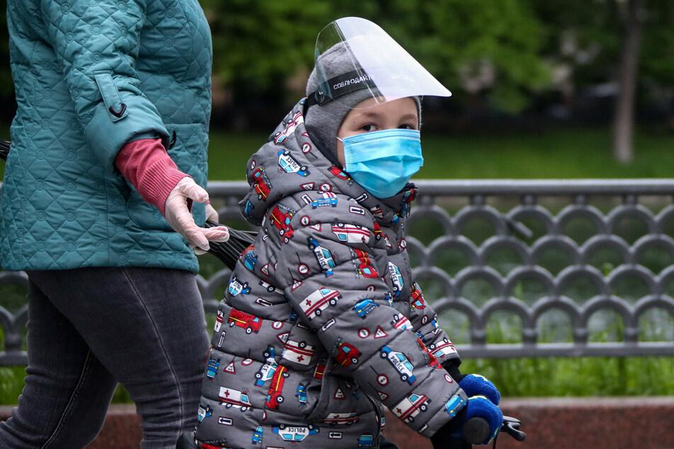 Ein Kind trägt eine Atemschutzmaske und ein Visier.