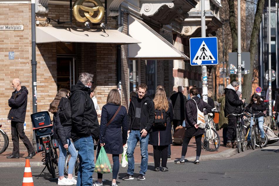 Menschen stehen vor einer Bäckerei in Hannover Schlange. Durch Maßnahmen zur Eindämmung des Coronavirus wird das öffentliche Leben in Niedersachsen massiv beeinträchtigt.