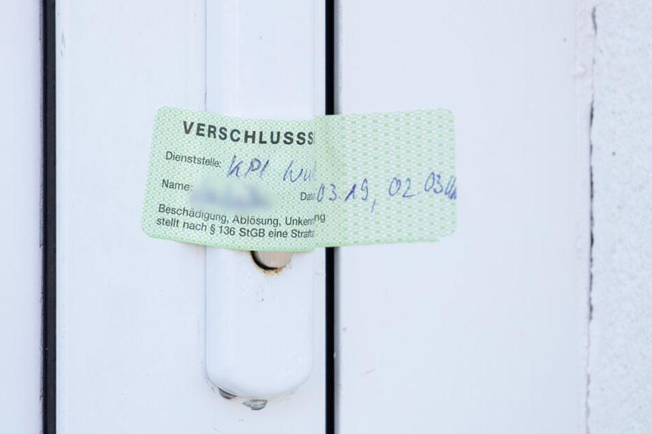 Ein Verschlusssiegel der Würzburger Polizei ist auf die Tür eines Wohnhauses geklebt, das zuvor durchsucht wurde.